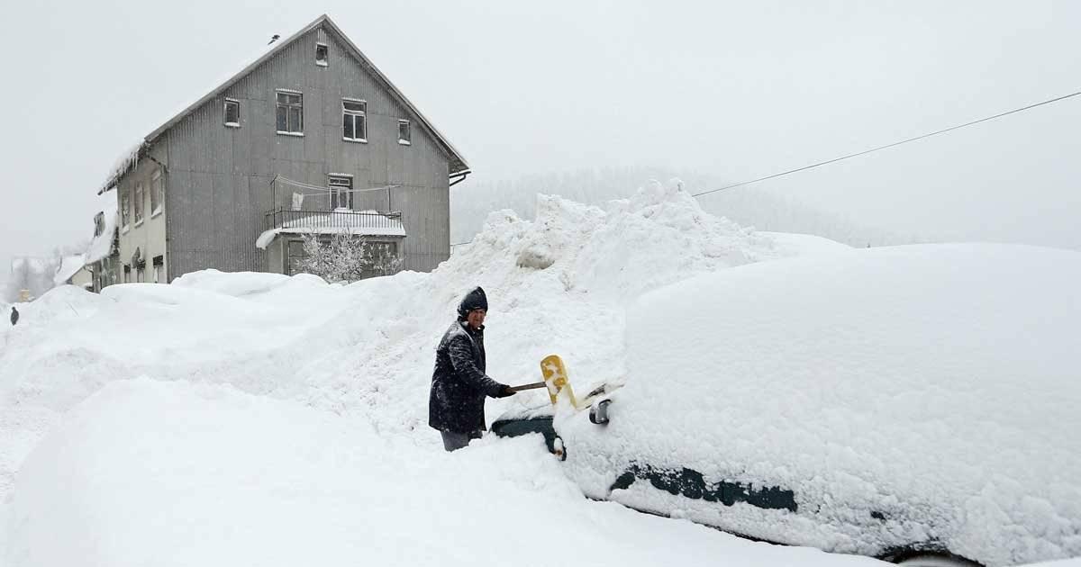 Homem tenta tirar a neve do carro REUTERS/Antonio Bronic