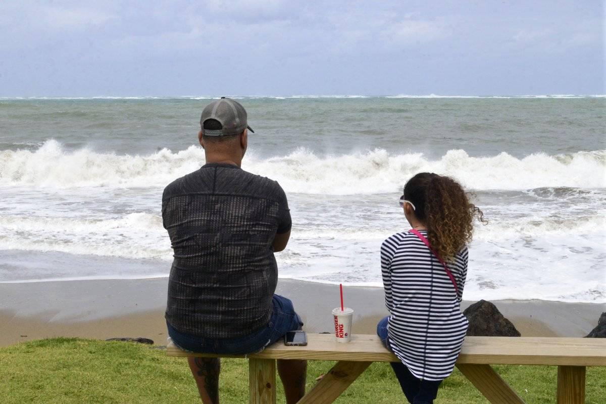 Foto: Una familia observa las olas romper en una playa de Dorado/Dennis A. Jones/Metro PR