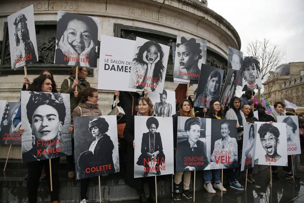 Mujeres sostienen carteles de feministas famosas (entre ellas Frida Kahlo)