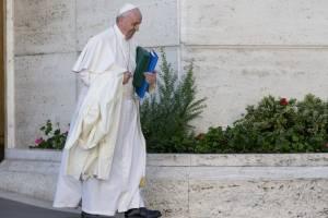 En esta foto de archivo del 24 de octubre de 2015, el Papa Francisco lleva su abrigo y documentos cuando se va después de una sesión matutina del último día del Sínodo de los obispos, en el Vaticano.