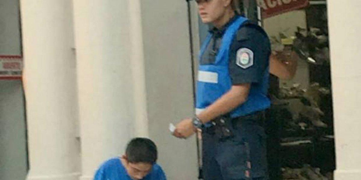 """""""Los lápices son mejores que las balas"""": La foto de un policía ayudando a hacer la tarea a un niño que todos aplauden"""
