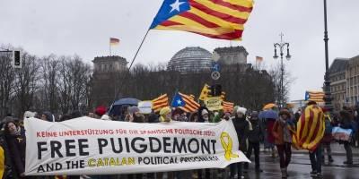 """Personas con una pancarta encabezan una protesta frente al edificio del Reichstag, condenando el arresto del expresidente de Cataluña, Carles Puigdemont en Alemania, en una manifestación en Berlín el domingo 1 de abril de 2018. La pancarta lee: """"No hay ap"""