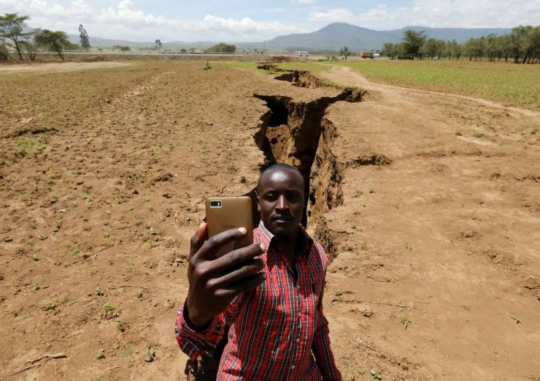 Homem posa para selfie com a enorme rachadura atrás (Foto: Thomas Mukoya/Reuters)