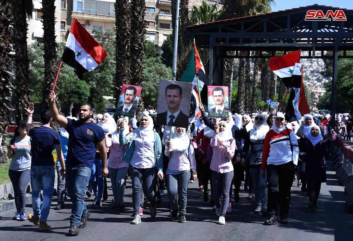 En esta imagen, distribuida por la agencia de noticias oficial de Siria, SANA, manifestantes sostienen banderas del país y retratos del presidente Bashar Assad durante una manifestación en apoyo de las fuerzas armadas sirias, en Damasco, el 16 de abril de