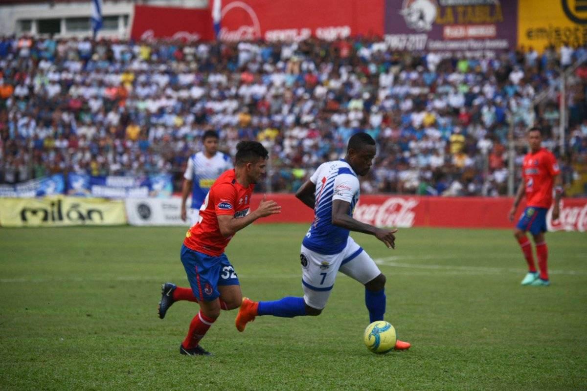 Jose Dos Santos conduce el balón ante Bryan Lemus