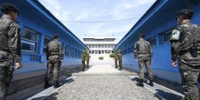 Cuatro soldados norcoreanos (centro-lejos) y cuatro soldados surcoreanos (derecha e izquierda) parados en la aldea fronteriza de Panmunjom en la zona desmilitarizada, Corea del Sur