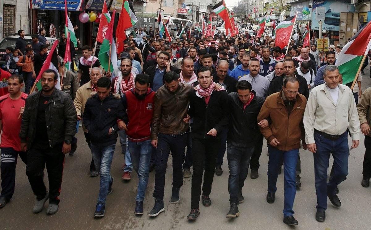 Los asistentes al entierro del periodista palestino Ahmed Abu Hussein, que murió tras recibir un disparo del ejército israelí cuando cubría las protestas en la frontera, muestran banderas palestinas durante el funeral celebrado en el campo de refugiados d