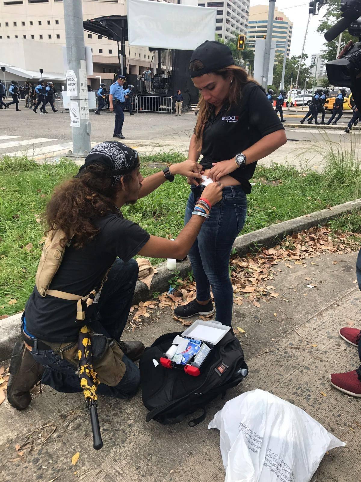 Manifestante ayuda a reportera herida en medio de protesta
