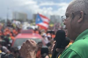 El presidente de la Union Independiente Auténtica (UIA), Pedro Irene Maymí, s dirige a los manifestantes antes de que comience la marcha. / Foto: David Cordero Mercado