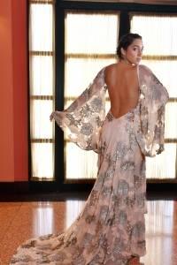 Vestido largo en tul nude, bordado en flores de lentejuelas con escote profundo en el frente y en la espalda. Accesorios: BVLGARI Dennis Jones