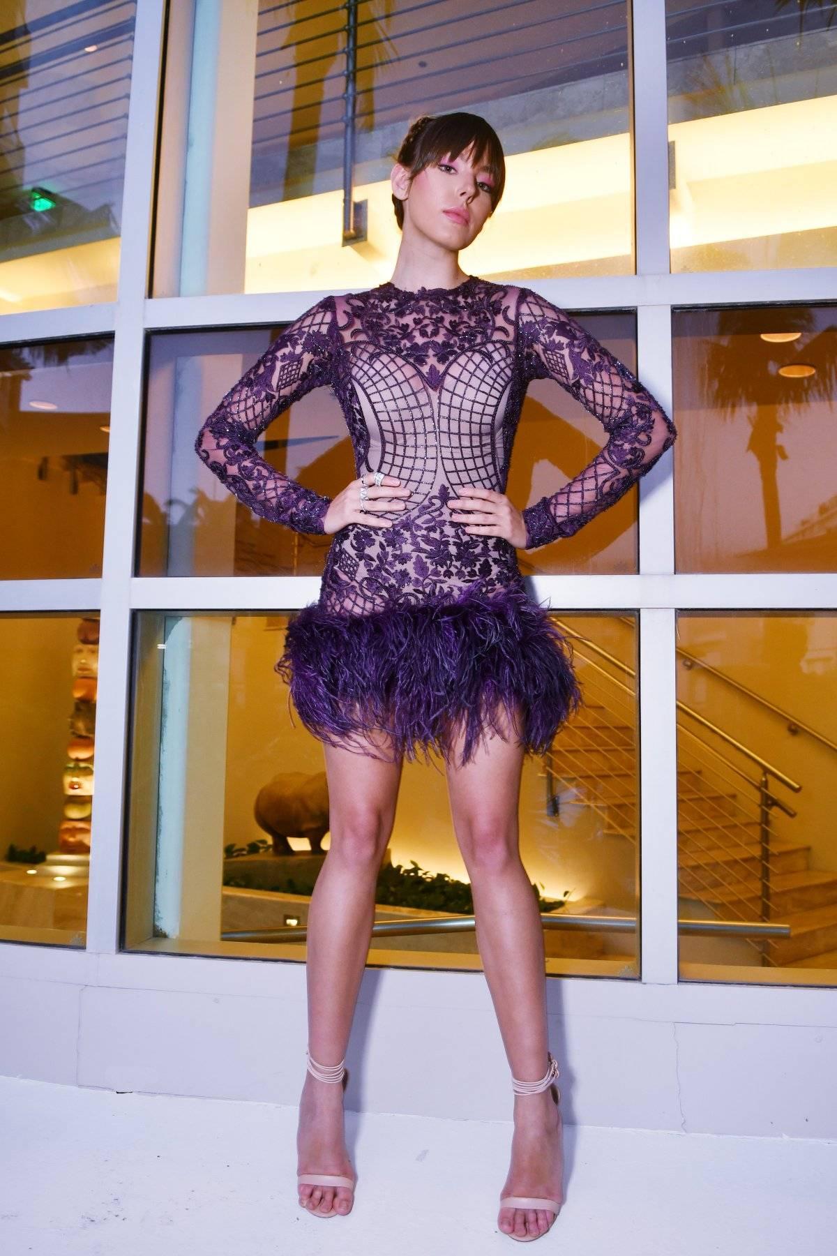 Vestido corto de mangas largas en tul bordado en canutillos y cristales, con plumas en el ruedo en el mismo tono. Accesorios: BVLGARI / Foto: Dennis Jones