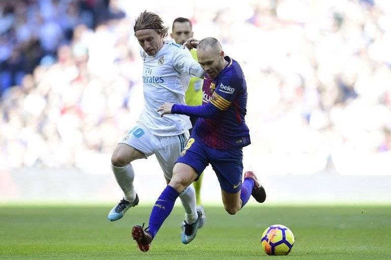 Rakitic trata de quitarle el balón a Iniesta