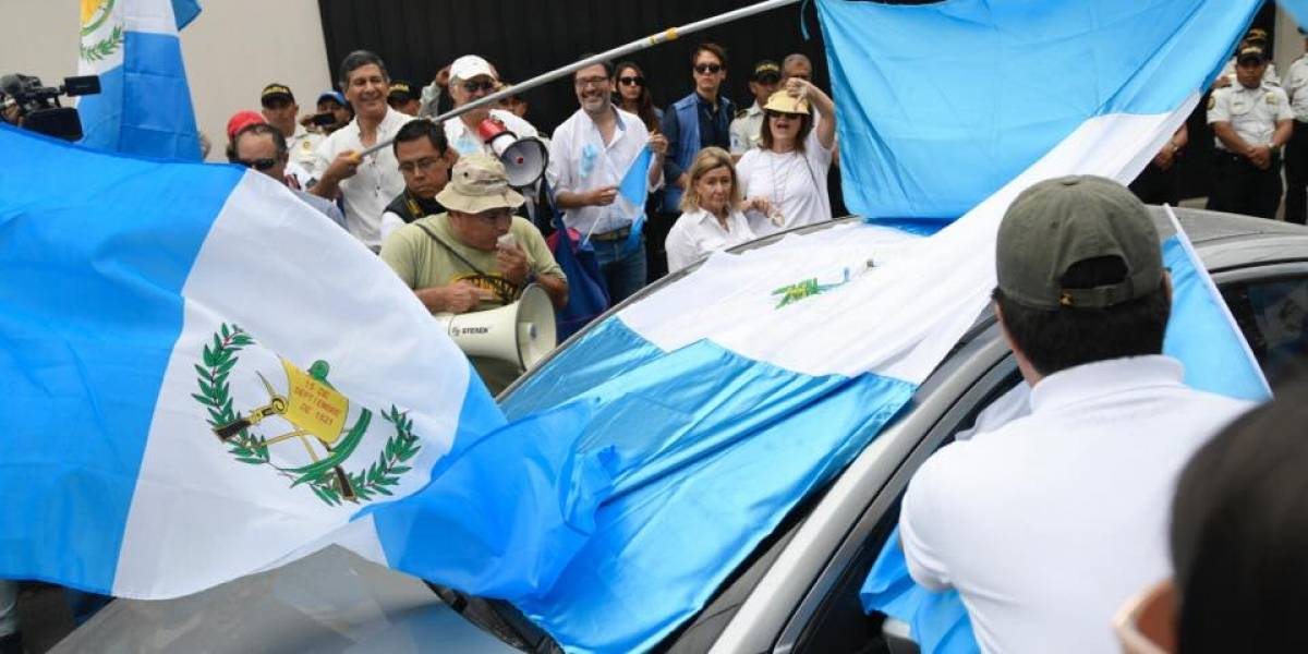 Carro sale de CICIG y bloquean su paso con una bandera de Guatemala