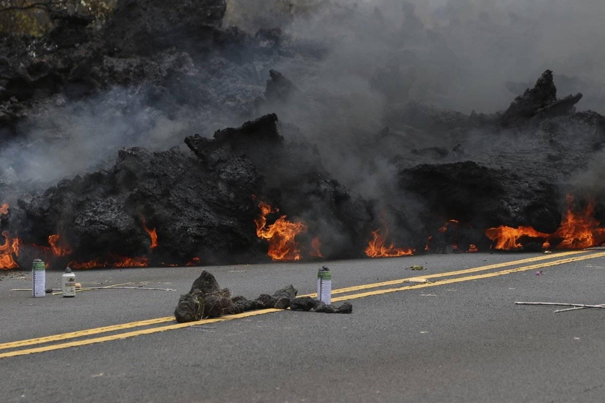 Esta fotografía del sábado, 5 de mayo de 2018, muestra cómo se quema la lava en una carretera, mientras que una ofrenda a la diosa del volcán se encuentra en primer plano en la subdivisión de Leilani Estates, cerca de Pahoa, Hawaii. (Foto AP / Caleb Jones)
