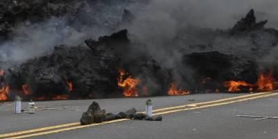 Esta fotografía del sábado, 5 de mayo de 2018, muestra cómo se quema la lava en una carretera, mientras que una ofrenda a la diosa del volcán se encuentra en primer plano en la subdivisión de Leilani Estates, cerca de Pahoa, Hawaii. (Foto AP / Caleb Jones