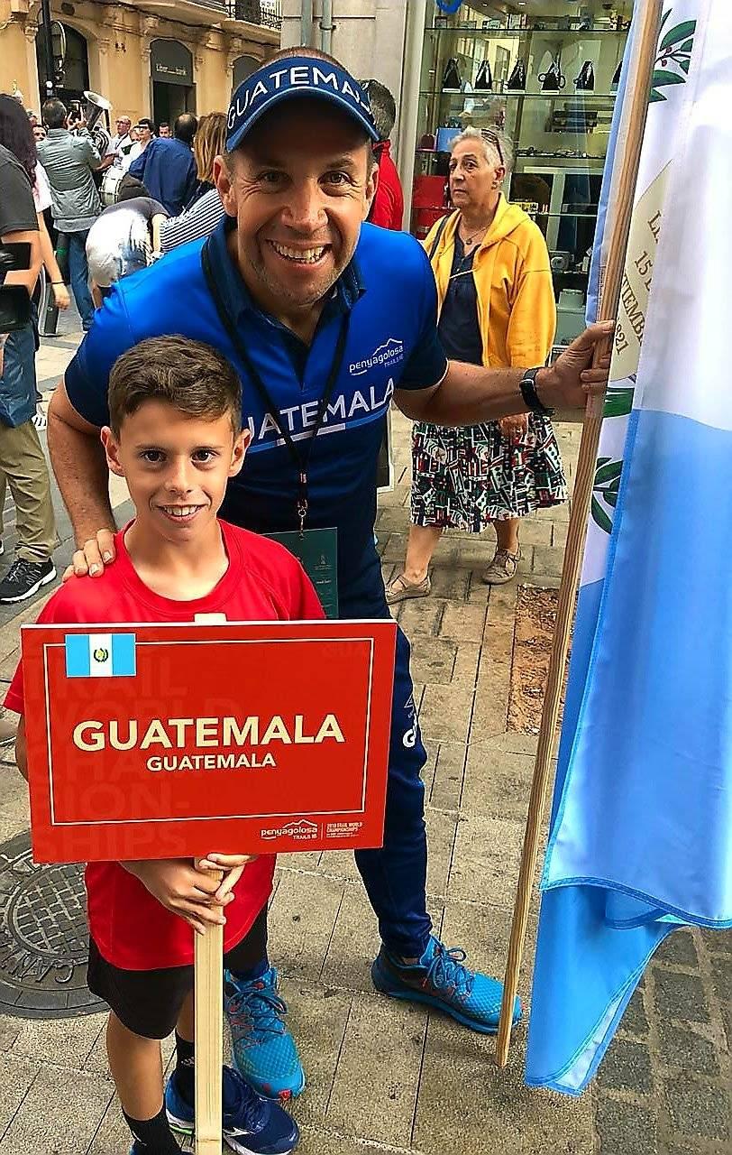 Sagastume junto a un niño que tiene un letrero con el nombre de Guatemala
