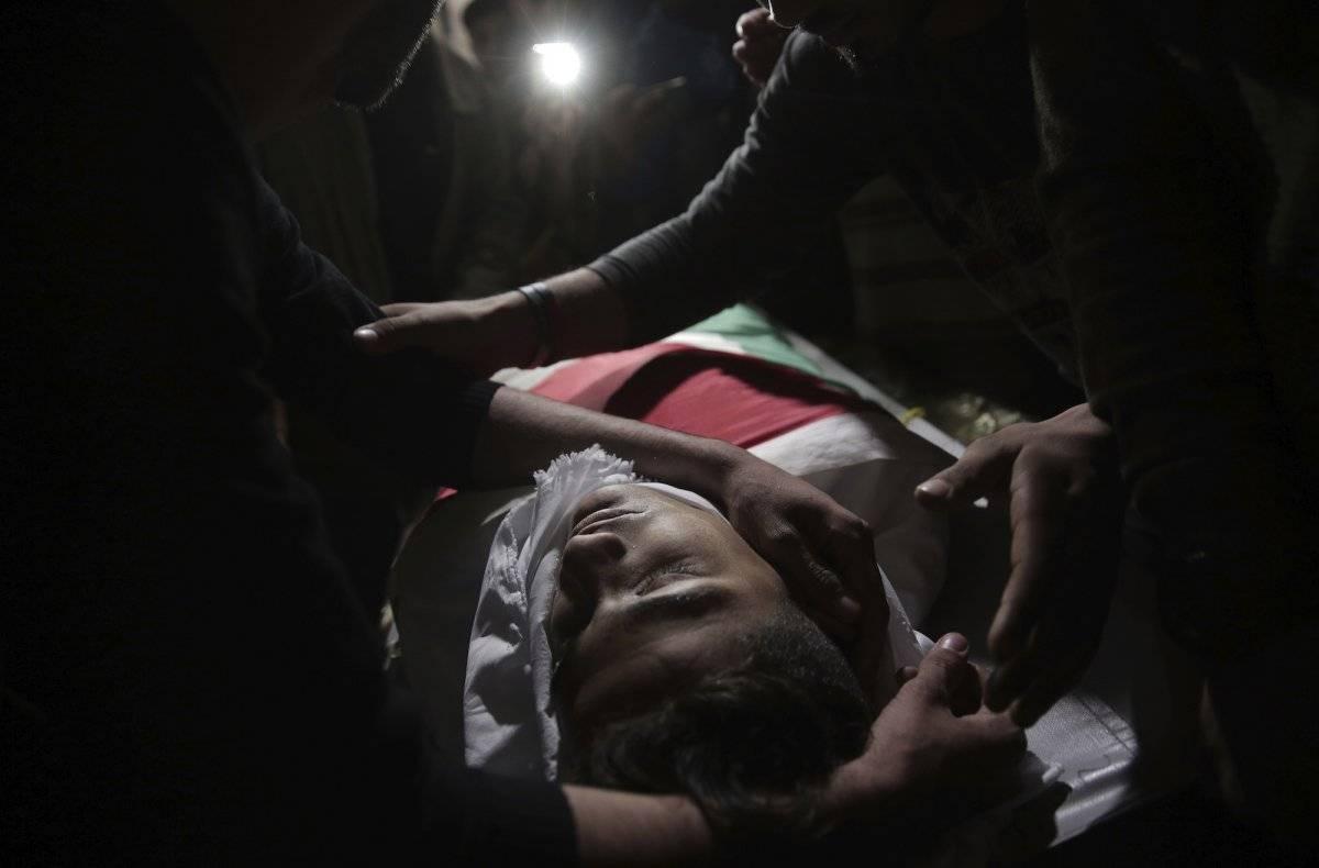 Familiares de Jamal Afaneh, un joven palestino de 15 años, velan su cuerpo en su casa durante su funeral, en el campo de refugiados de Rafah, en el sur de la Franja de Gaza, el 13 de mayo de 2018. Afaneh falleció tras ser baleado por soldados israelíes du