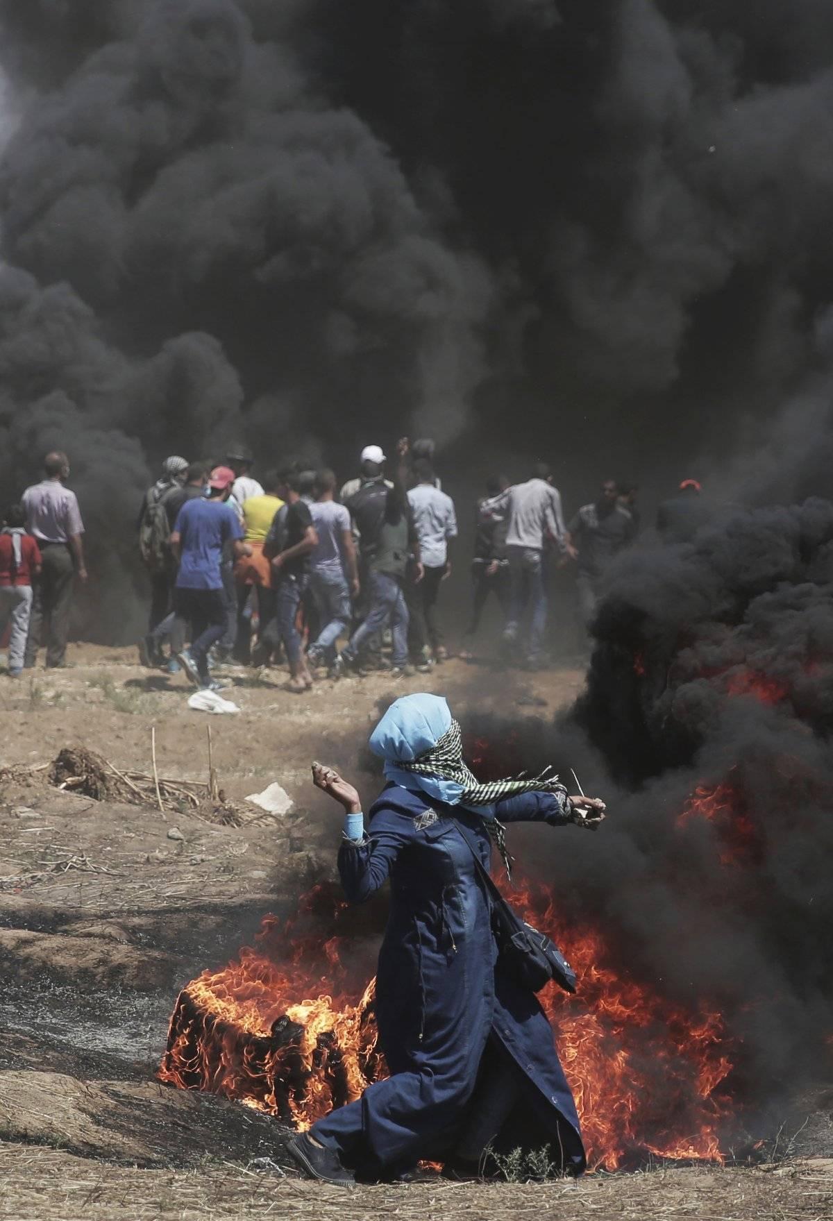 Una mujer palestina arroja piedras contra las tropas israelíes durante una protesta en la frontera de la Franja de Gaza con Israel, el lunes 14 de mayo de 2018. El fuego israelí ha matado a decenas de palestinos durante protestas masivas a lo largo de la