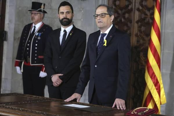 El nuevo presidente catalán, Quim Torra, hace su juramento durante una ceremonia de investidura junto al presidente del Parlamento catalán Roger Torrent en el Palau Generalitat de Barcelona, el jueves 17 de mayo de 2018.