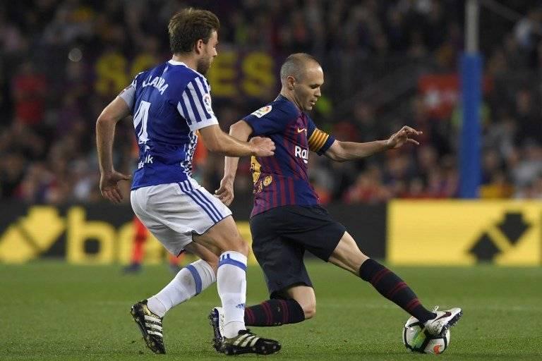 Iniesta protege el balón ante la marca de un adversario