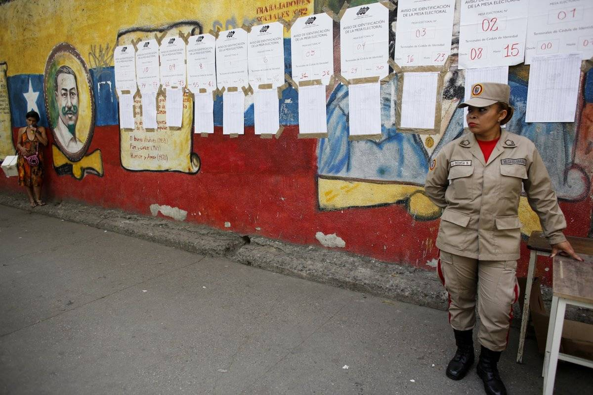 Un miembro de la milicia bolivariana se detiene frente a las listas de votantes en un centro electoral durante los comicios presidenciales en Caracas, Venezuela, el domingo 20 de mayo de 2018. (Foto: AP/Ariana Cubillos)
