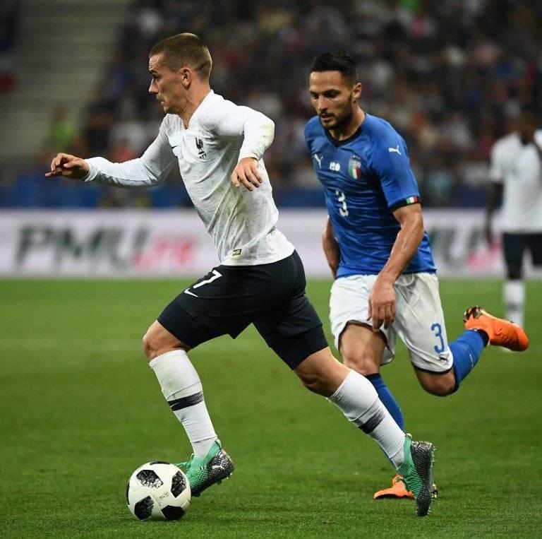 Antoine Griezmann conduce el balón ante la mirada de un italiano