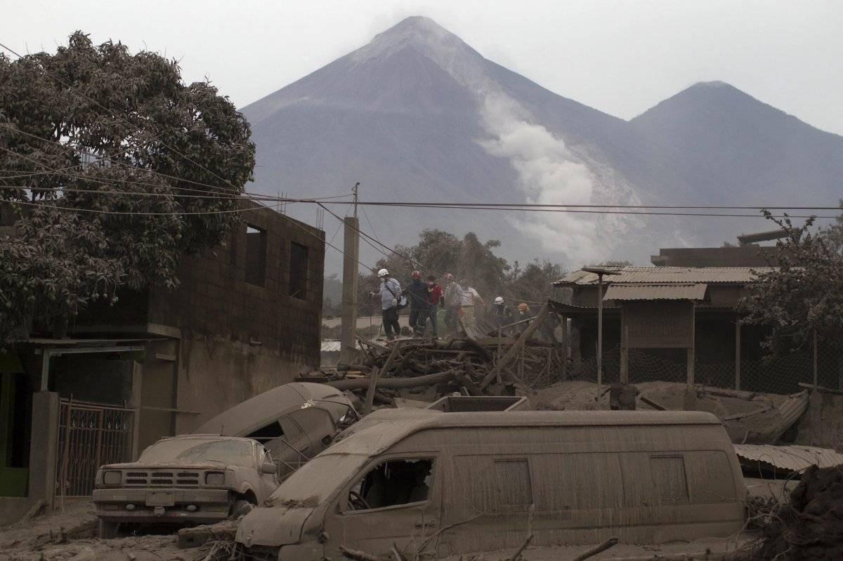 """Rescatistas caminan por los tejados de Escuintla, Guatemala, el lunes 4 de junio de 2018, cubierto con cenizas pesadas arrojadas por el Volcán de Fuego, o """"Volcán de fuego"""", en el fondo, en el centro izquierdo. (Foto AP / Luis Soto)"""