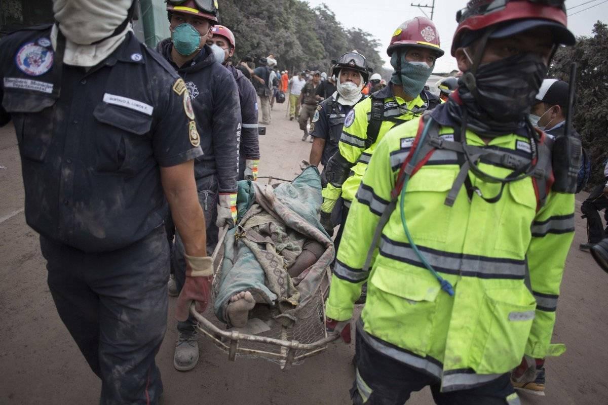 Los bomberos llevan un cuerpo recuperado cerca del Volcán de Fuego, en Escuintla, Guatemala, el lunes 4 de junio de 2018. Una ardiente erupción volcánica en el centro-sur de Guatemala envió lava a las comunidades rurales, matando al menos a 25 mientras lo
