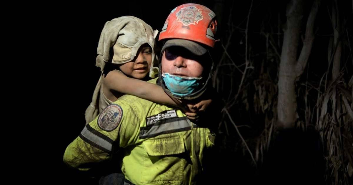 Agente da força de resgate retira criança de área de risco em El Rodeo, região atingida pela erupção do vulcão, na Guatemala Foto: REUTERS/Luis Echeverria