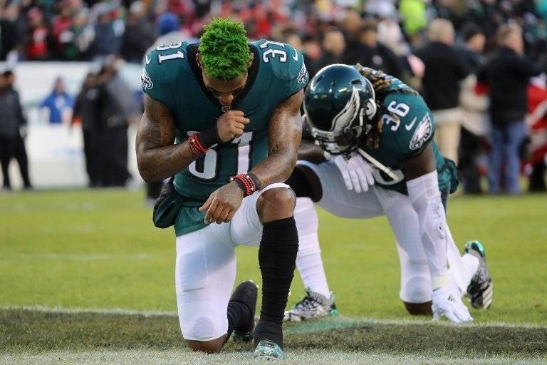 Jugadores de los Eagles se arrodillan durante el himno