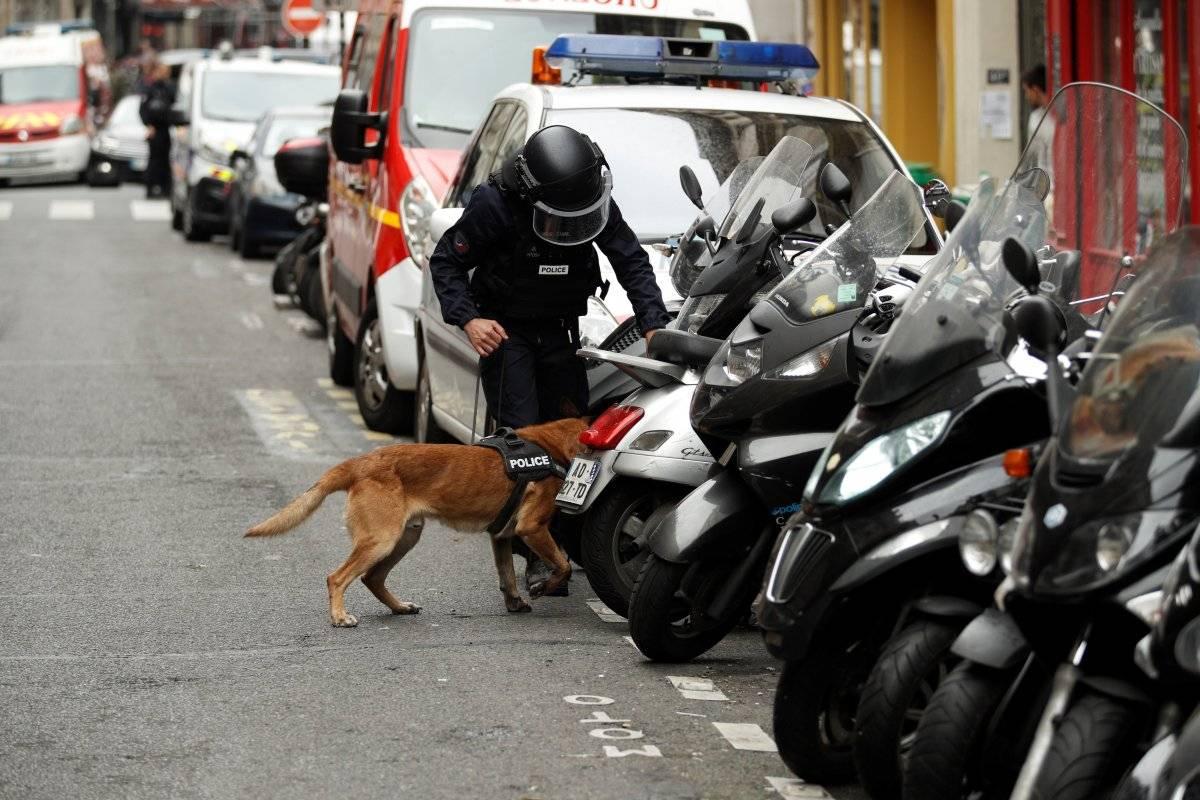 Un miembro de las fuerzas policiales y su perro rastreador registran las calles parisinas durante una supuesta toma de rehenes en la Rue des Petites Ecuries, en París, Francia. Foto: EFE