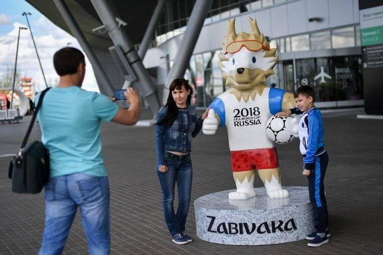 Dos aficionados posan junto a la mascota de Rusia 2018
