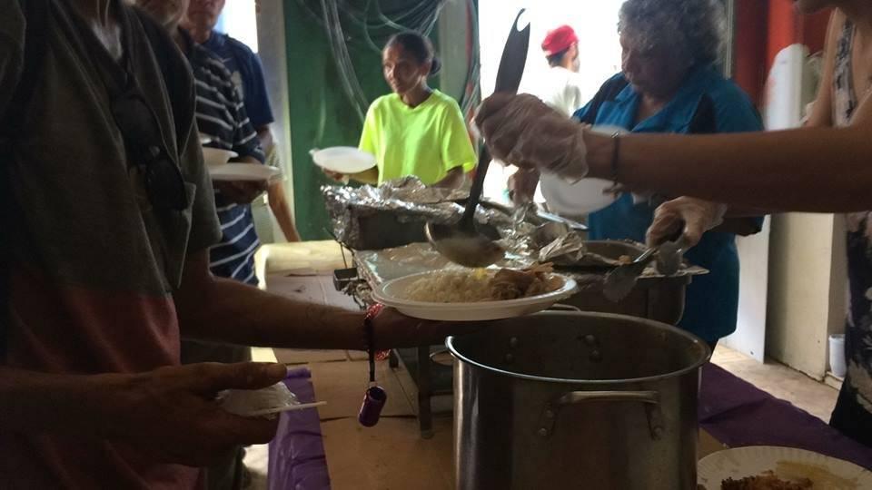 Foto: Voluntarios del CAM reparten la comida a las personas que llegan al lugar/Tomada de Facebook/CAM