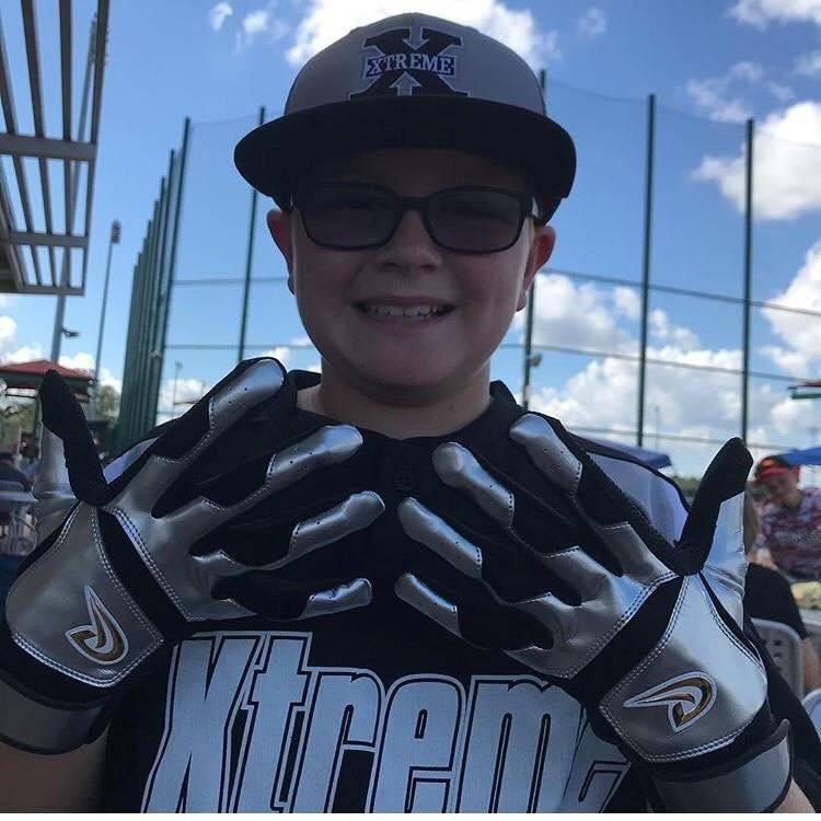 Foto: Otro niño jugador de béisbol enseña sus guatillas de la marca boricua/Du xSports