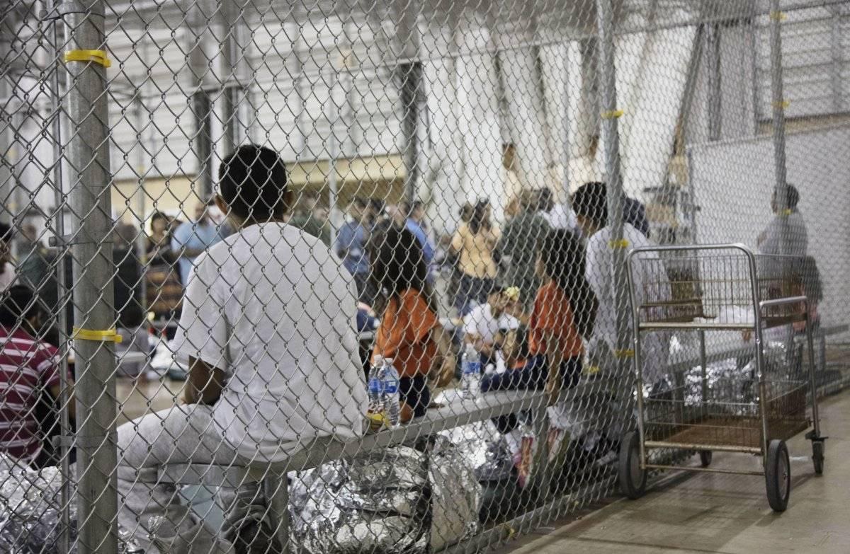 En esta fotografía proporcionada por la Oficina de Aduanas y Protección Fronteriza de Estados Unidos, personas que han sido detenidas por intentar entrar al país sin autorización, están sentadas en una de las jaulas en el centro de McAllen, Texas, el domi