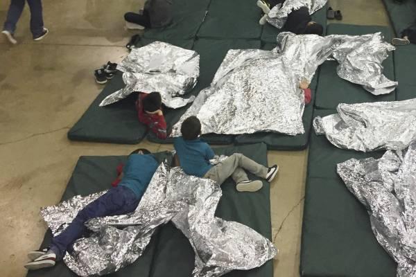 En esta fotografía proporcionada por la Oficina de Aduanas y Protección Fronteriza de Estados Unidos, personas que han sido detenidas por intentar entrar al país sin autorización, descansan en una de las jaulas en el centro de McAllen, Texas, el domingo 1