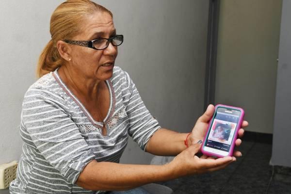 Alicia Rodríguez muestra una foto de su madre, Cándida Arguinzoni Ríos, quien no ha sido incluida en la lista oficial de muertes por María, a pesar de que así lo establece su certificado de defunción. / Foto: Dennis Jones