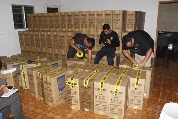 Agentes policiales embalan cargamento de cigarros de contrabando.