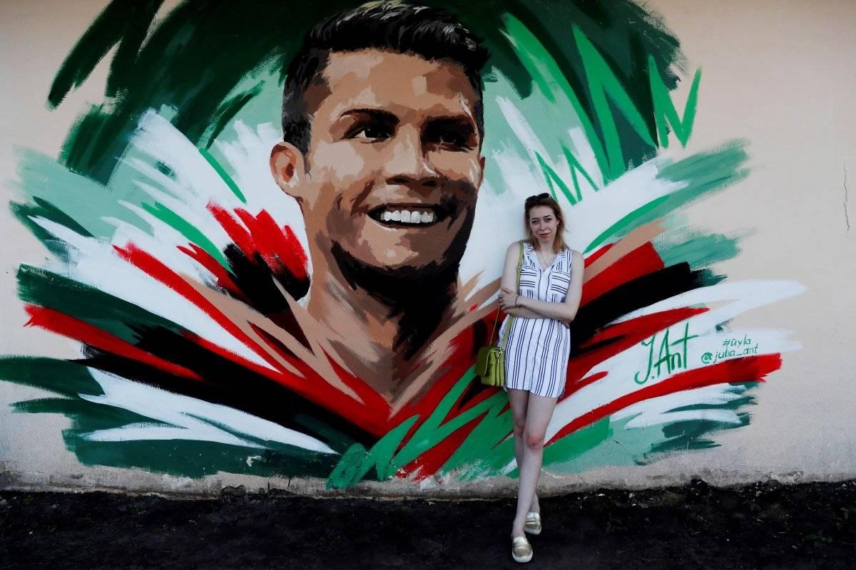 La artista rusa Julia Antipova posa frente al mural que creó del futbolista portugués Cristiano Ronaldo, en Saransk, Rusia, hoy, 24 de junio de 2018. Julia creó este muro en honor a Ronaldo, quien se enfrentará con su selección a Irán en su correspondiente partido de la tercera jornada de la fase de grupos del Mundial de Rusia 2018. EFE/Esteban Biba