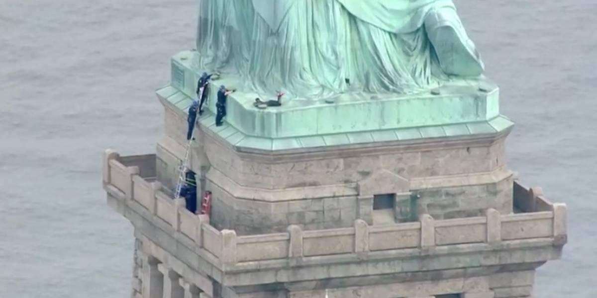 Mujer escala la Estatua de la Libertad en forma de protesta