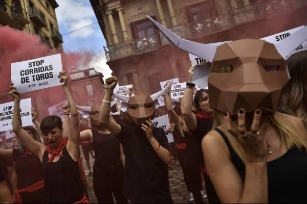 Rodeadas de humo rojo, manifestantes protestas contra la lidia de toros frente al ayuntamiento de Pamplona, en la víspera del inicio de los Sanfermines, el 5 de julio de 2018. (
