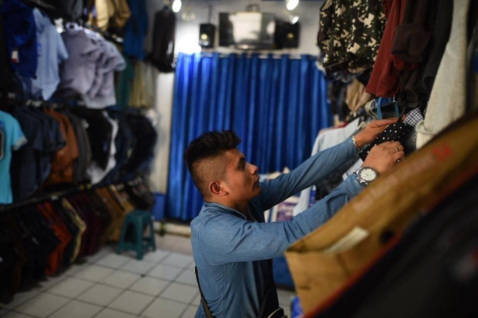 Lessther Avalos ordena la ropa en su tienda