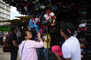 Una persona observa una producto en una venta de gorras