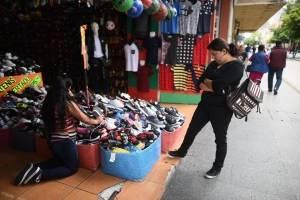Una mujer observa los zapatos en un negocio de la Sexta Avenida