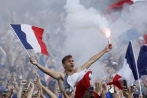 Un aficionado francés mantiene una bengala en el festejo de campeón