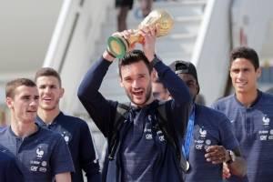 Hugo Lloris muestra la copa de campeón en su arribo al aeropuerto