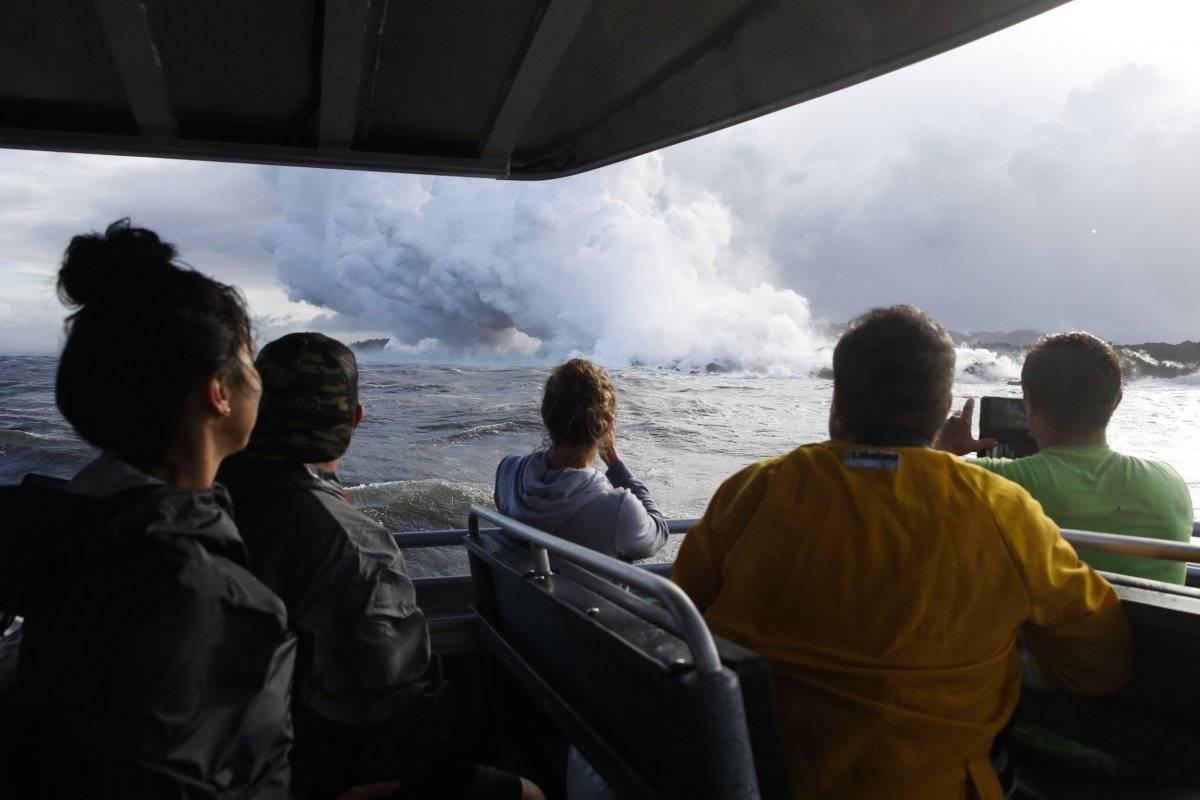 En esta fotografía del 20 de mayo de 2018 se muestra a un grupo de turistas que observan la lava que se interna en el océano, cerca de Pahoa, Hawai. (AP Foto/Jae C. Hong, Archivo)