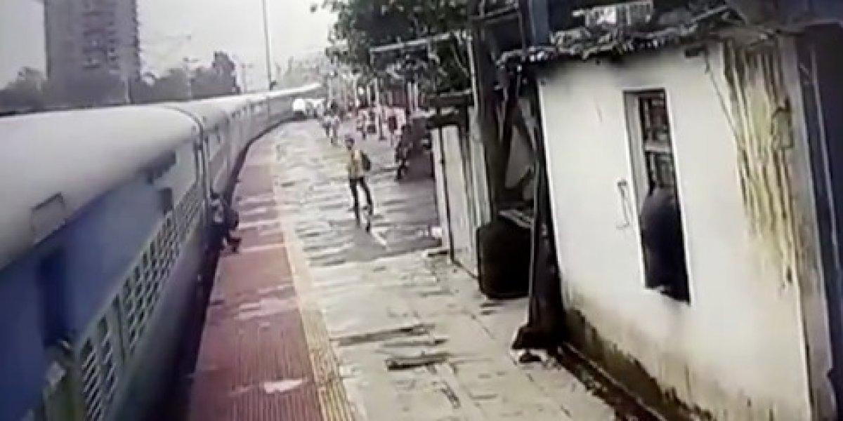 Un tren arrastra a un joven a lo largo de un andén en la India