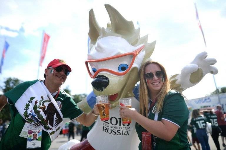 Dos aficionados mexicanos se toman una foto con la mascota del Mundial