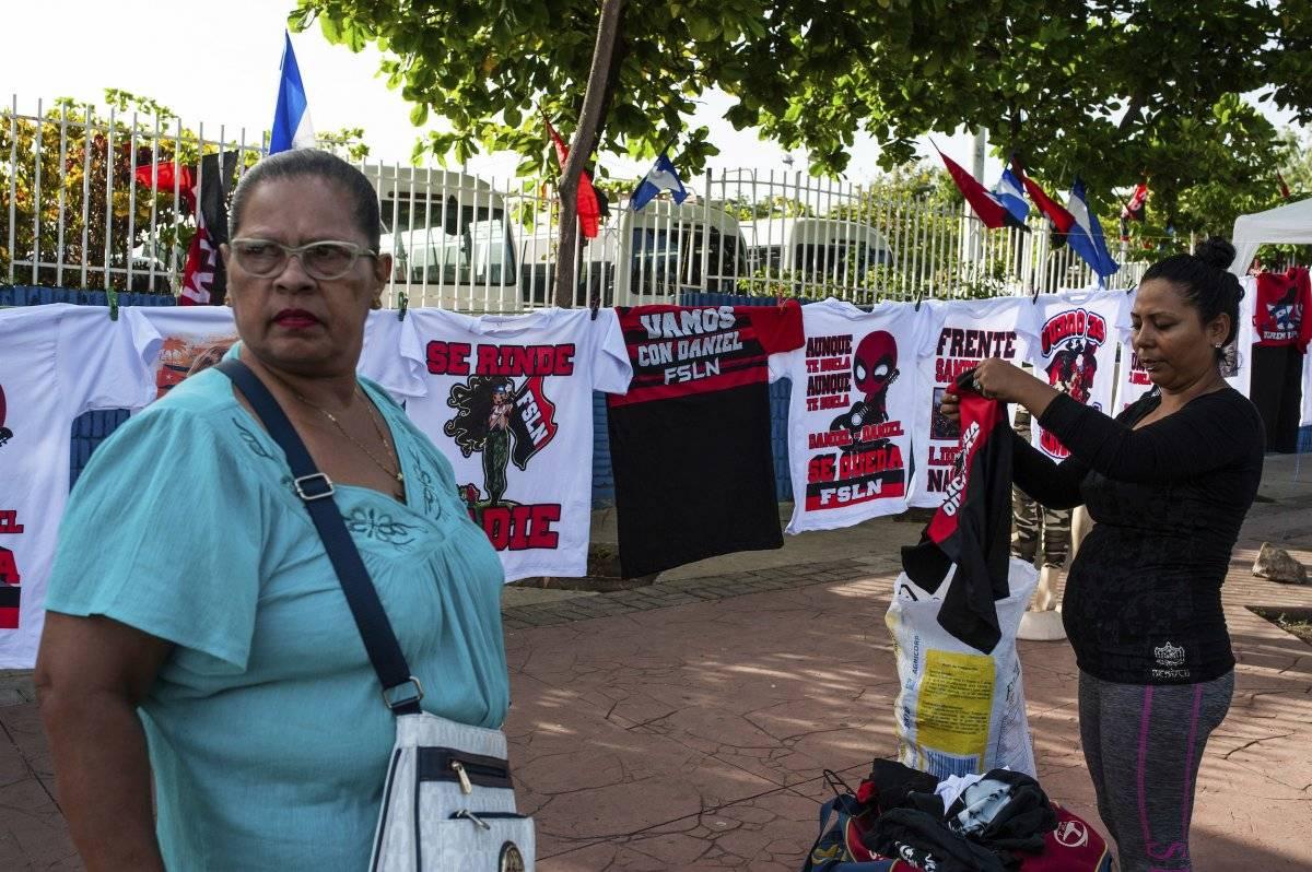 Un vendedor muestra camisetas promocionando al presidente nicaragüense Daniel Ortega y al partido gobernante Frente Sandinista de Liberación Nacional, antes de una concentración conmemorativa del levantamiento que derrocó a la familia Somoza, en Managua, Nicaragua, el jueves 19 de julio de 2018. (AP Foto / Cristobal Venegas)